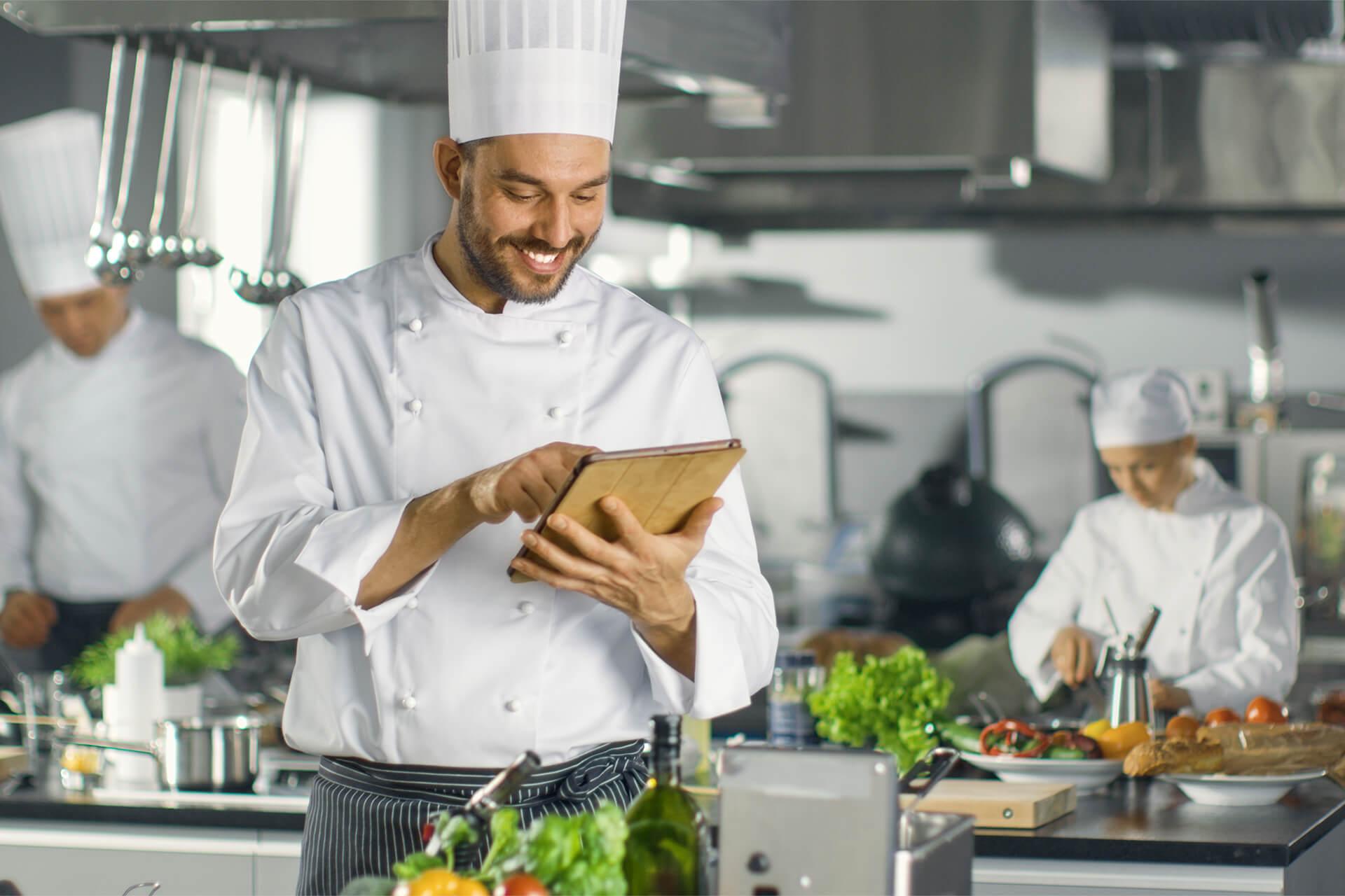 three chiefs working in a busy restaurant kitchen
