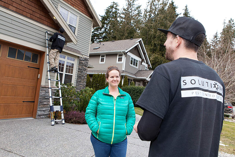 Solutions Pest Control team talking to home owner in front of home