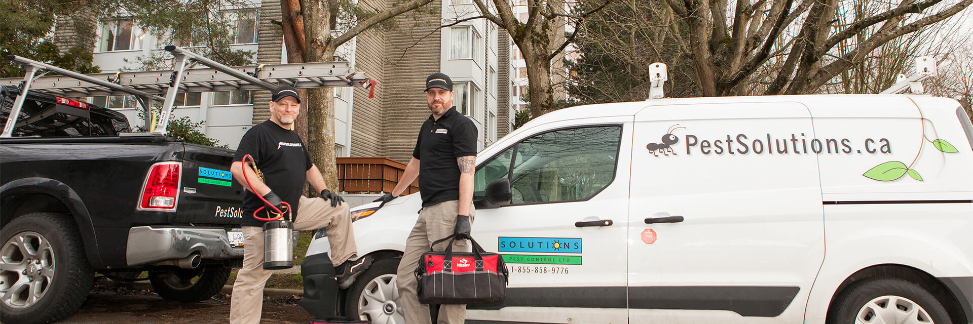 Solutions Pest Control service technicians with their trucks outside large condo building